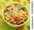 closeup of a bowl with refreshing pasta salad on a draped table with a green tablecloth - stock photo