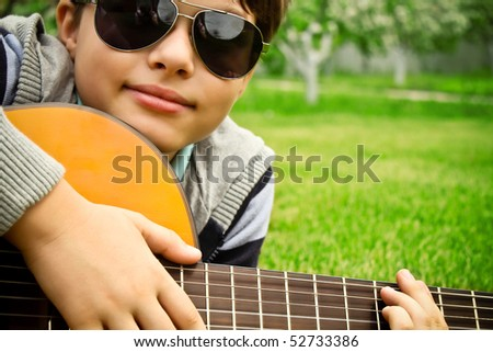Closeup of a boy in sunglasses playing the guitar - stock photo