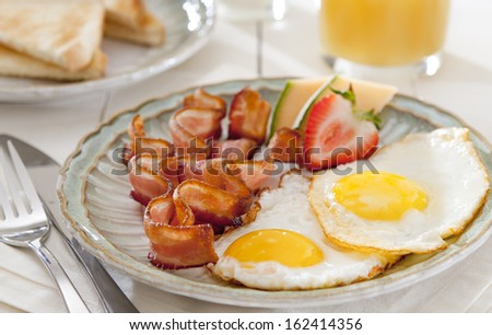 Closeup of a breakfast table with bacon, eggs and fruit.