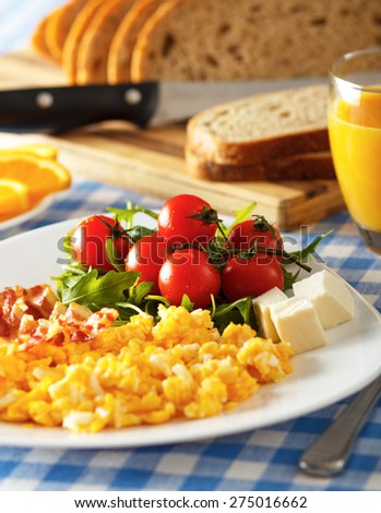 Closeup of a breakfast table with bacon, scrambled eggs, fruit and orange juice. - stock photo