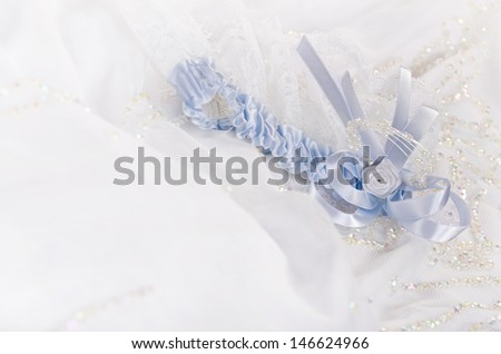 Closeup of a bridal garter with lace trim and blue satin bow against white wedding dress - stock photo
