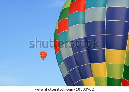 Closeup of a bright hot air balloon, with another one in the distance. - stock photo