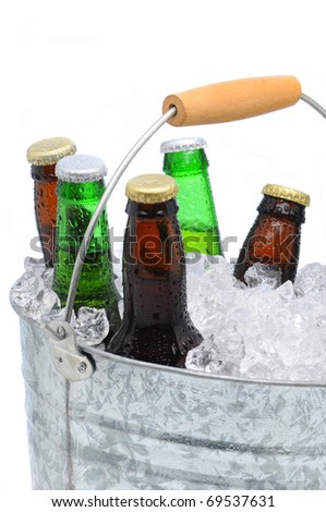 Closeup of a bucket  filled with ice cubes and an assorted beer bottles on a white background. - stock photo