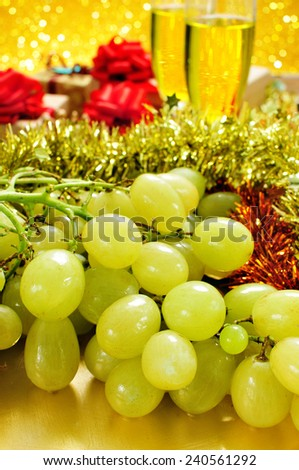 closeup of a bunch of grapes and glasses with champagne and some gifts in the background for the traditional celebration of the New Year in Spain - stock photo