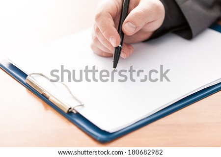 Closeup of a business man's hand with pen on the desk. Copy space for text.