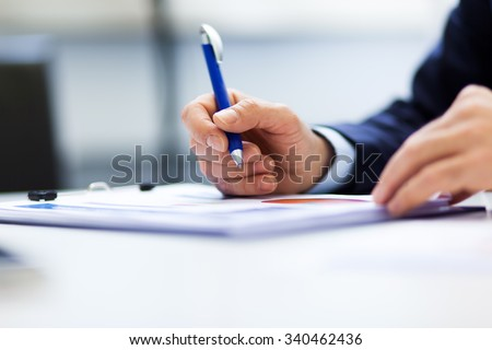 Closeup of a businessman at work on some documents - stock photo