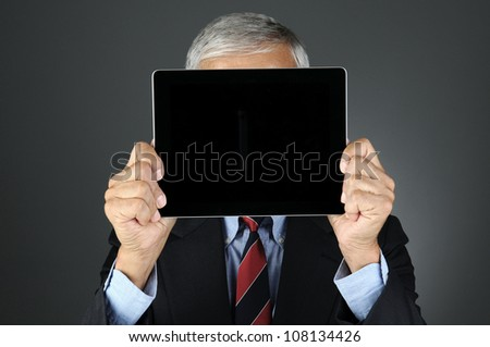 Closeup of a businessman holding his tablet computer with blank screen in front of his face.. Horizontal format over a light to dark gray background. Man is unrecognizable. - stock photo