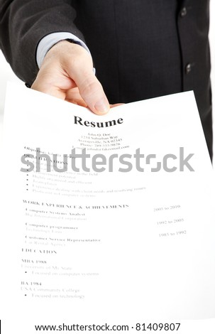 Closeup of a businessman's hand holding out a resume.  Focus on the hand and the word Resume. - stock photo
