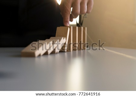 Closeup of a businessman stopping domino effect with his finger at sunset.