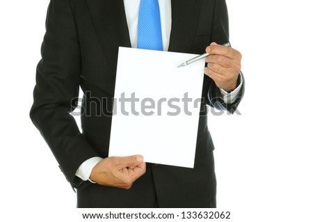 Closeup of a businessman using his pen to point at the blank sheet of paper he is holding. Man is unrecognizable, torso only, over a white background. - stock photo