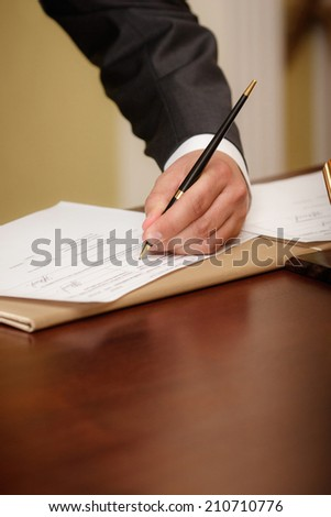 Closeup of a businessman writing on agenda - stock photo