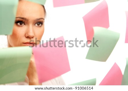 Closeup of a businesswoman looking at stickers, isolated on white background - stock photo