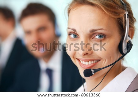 Closeup of a businesswoman with headset, her colleagues at the background. - stock photo