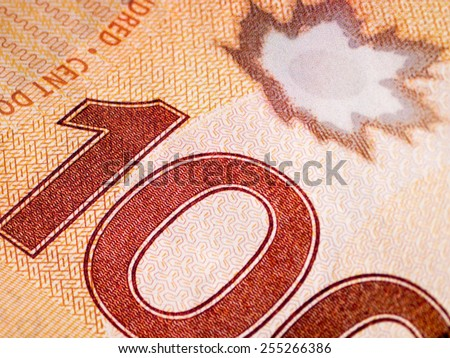 Closeup of a Canadian 100 Dollar Bill showing the digits and maple leaf emblem - stock photo