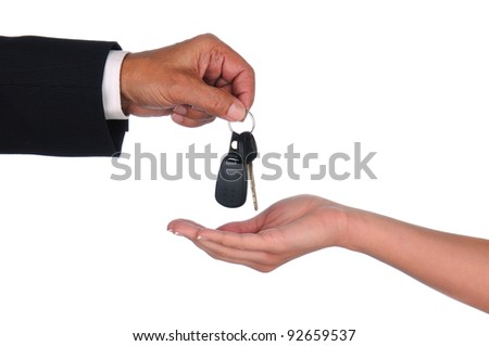 Closeup of a car salesman dropping keys into a woman's waiting hand. Horizontal format showing hands only over a white background