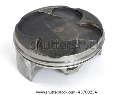 Closeup of a carbon-coated and damaged motorcycle piston isolated on white background. - stock photo