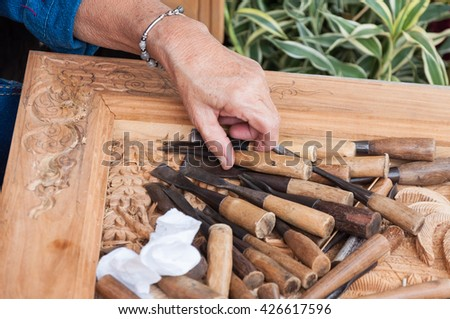 Closeup of a carpenter hands working with a chisel and hammer on wooden workbench,wood handcraft Thailand style, carpenter (Public area , show for all people) - stock photo