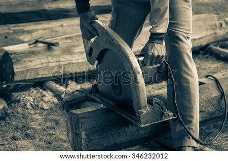 Closeup of a carpenters hands working with electric circular saw cutting wood, vintage color tone