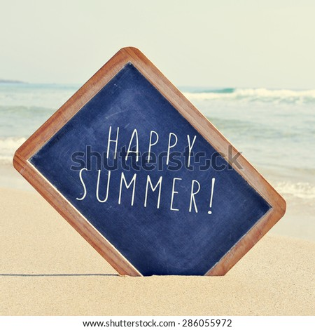 closeup of a chalkboard with a wooden frame and the text happy summer written in it, placed on the sand of a beach, with a retro effect - stock photo
