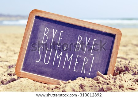 closeup of a chalkboard with the text bye, bye summer written in it, on the sand of a beach - stock photo