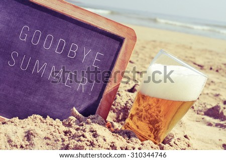 closeup of a chalkboard with the text goodbye summer written in it and a glass of beer, on the sand of a beach - stock photo