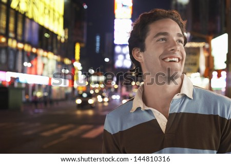 Closeup of a cheerful young man in Times Square New York at night - stock photo