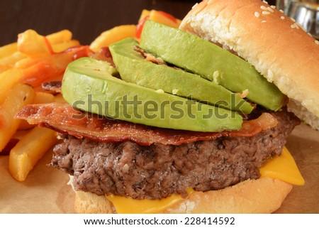 Closeup of a cheese burger with bacon and avocado - stock photo