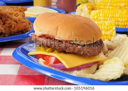 Closeup of a cheeseburger on a picnic table - stock photo