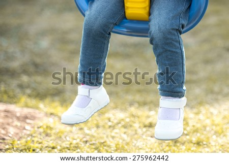 closeup of a child's legs hanging from a swing in the park - stock photo