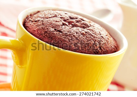 closeup of a chocolate mug cake in a yellow porcelain mug on a set table covered with a checkered tablecloth - stock photo