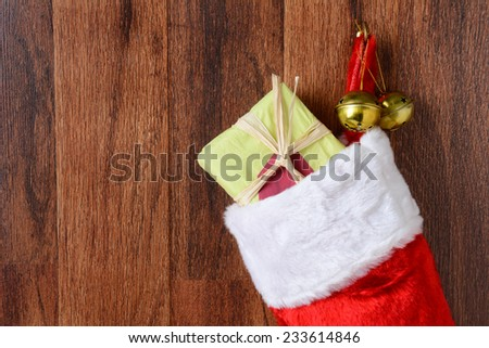 Closeup of a Christmas stocking filled with presents hanging from a hook on a wood wall. Two jingle bells hang from the hook also in vertical format. - stock photo