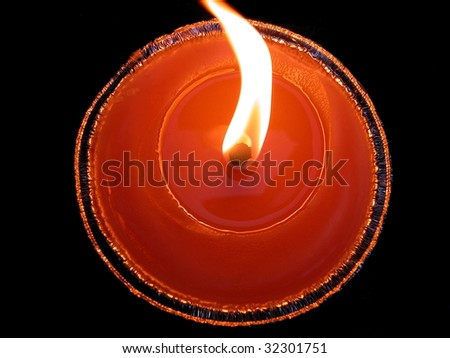 Closeup of a circular red candle on black background