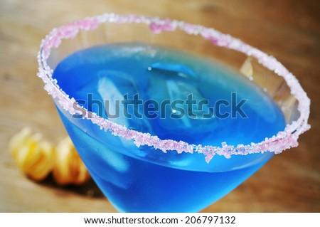 closeup of a cocktail glass with a blue beverage and a pink sugar rim - stock photo