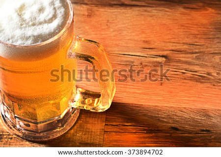 Closeup of a cold beer mug with a foamy head and copy space. High angle view with warm side light and reflections on wood table. - stock photo