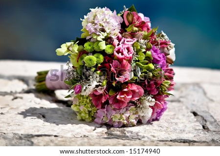 Closeup of a colorful wedding bouquet with the sea in the back. - stock photo