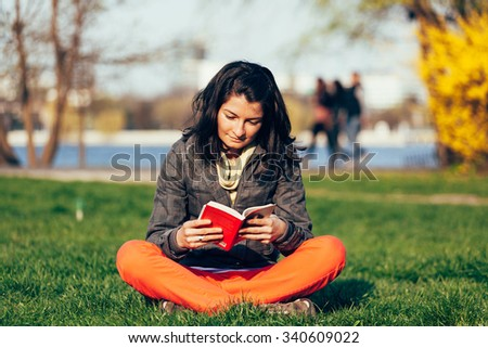 Closeup of a concentrated woman reading a book while sitting on the grass - stock photo