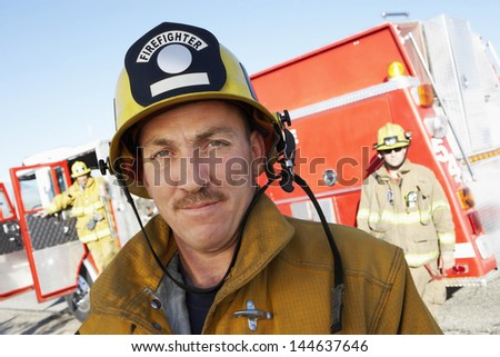 Closeup of a confident fire fighter standing in front of colleagues and fire engine - stock photo