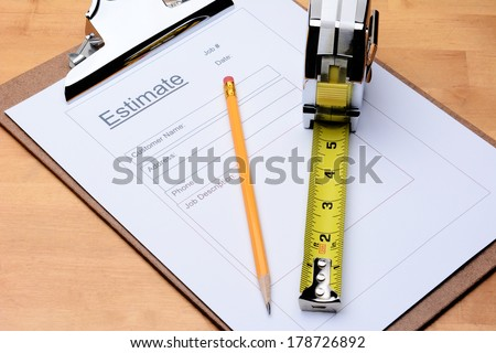 Closeup of a Contractors estimate form with a pencil and tape measure on a wooden table. Horizontal format filling the frame. - stock photo