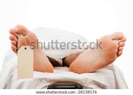 Closeup of a corpse on a gurney wearing a toe tag.  Isolated with clipping path. - stock photo