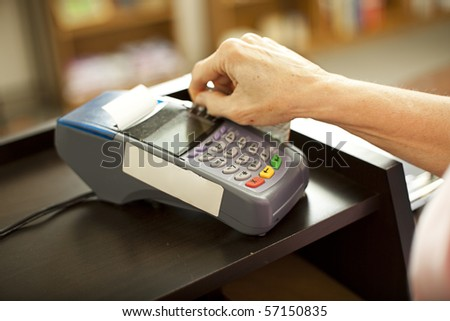Closeup of a credit card scanning machine in use.  Shallow depth of field.