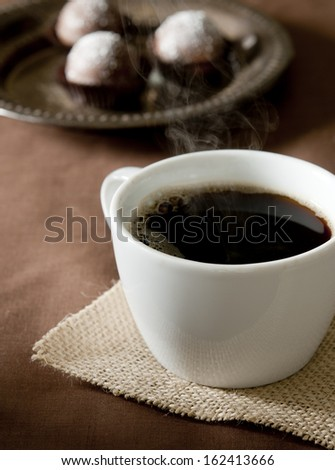 Closeup of a cup of steaming hot coffee with chocolate truffles in the background. - stock photo