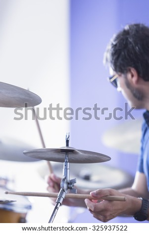 closeup of a cymbal with an unfocused drummer playing the drums on background in a recording studio - focus on the cymbal - stock photo