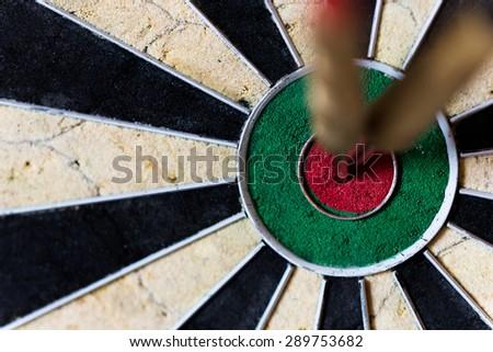 closeup of a Dartboard with Steeldarts in bullseye - stock photo