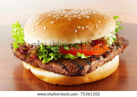 closeup of a delicious hamburger with salad and tomato on wood grain - stock photo