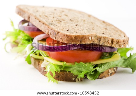 closeup of a deliciously looking sandwich with cheese, lettuce, red onion, tomato . Looking healthy.  Grainy sandwich. - stock photo