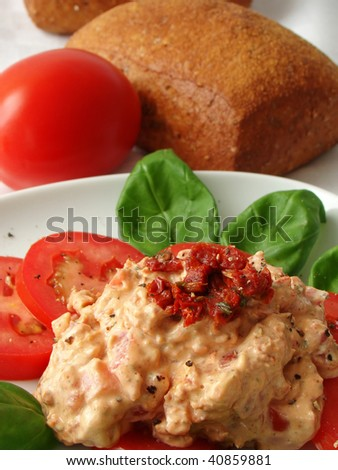 Closeup of a dip made from tomatoes, basil and cream cheese. Typical starter for a buffet or party but also for breakfast.