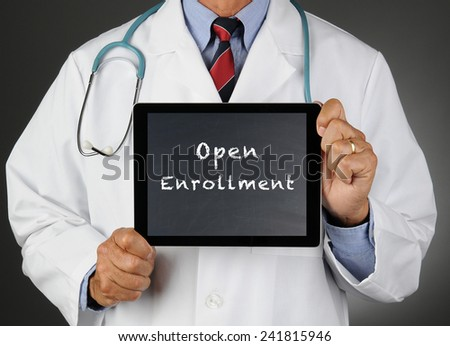 Closeup of a doctor holding a tablet computer with a chalkboard screen with the words Open Enrollment. Man is unrecognizable.  - stock photo