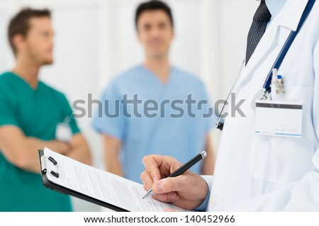Closeup Of A Doctor Writing Reports On A Paper - stock photo