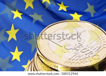 Closeup of a euro coin with a European flag in the background. - stock photo