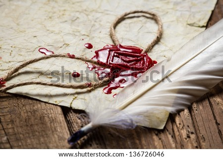 Closeup of a feather and red sealing wax - stock photo